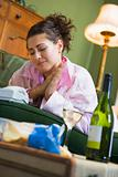 A young woman in her pyjamas drinking wine and watching her tele