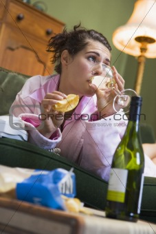 A young woman in her pyjamas drinking wine