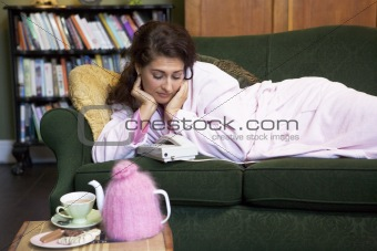 A young woman lying on her couch watching the phone