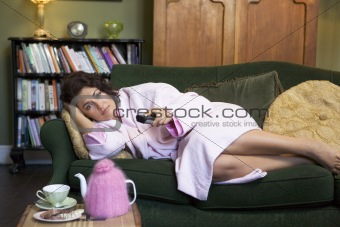 A young woman lying on her couch watching television