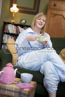 A young woman sitting on her couch drinking tea