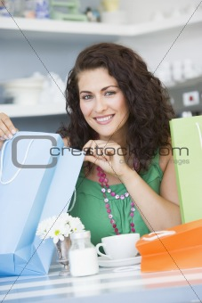 A young woman with shopping bags sitting in a cafe