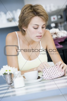 A young woman sitting in a cafe looking into her purse