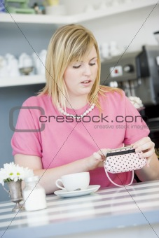 A young woman sitting in a cafe looking worried into her purse