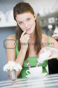 A young woman sitting in a cafe pouring sugar into her tea