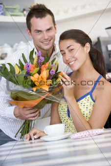 A young man giving flowers to a young woman in a cafe