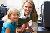 Teacher helping kindergarten children learn how to use computers