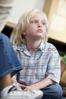 Boy daydreaming at kindergarten