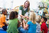 Kindergarten teacher and children looking at seedling in library
