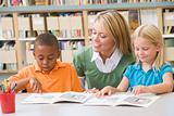 Kindergarten teacher helping students with reading skills