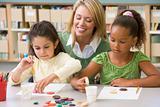 Kindergarten teacher sitting with students in art class,