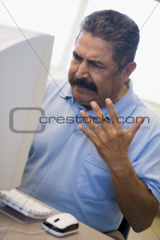 Mature male student expressing frustration at computer