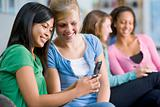 Teenage girls looking at a mobile phone