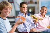 Teenage boys enjoying fast food lunches together