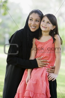 A Middle Eastern woman and her daughter sitting in a park