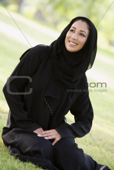 A Middle Eastern woman sitting in a park