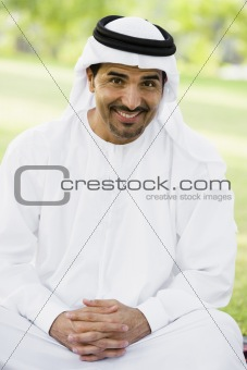 A Middle Eastern man sitting in a park