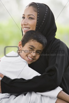 A Middle Eastern woman and her son sitting in a park