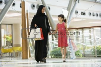 A Middle Eastern woman with a girl in a shopping mall