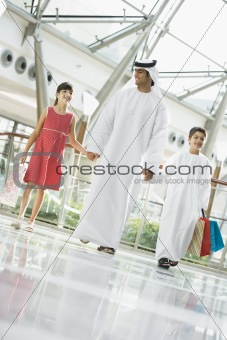 A Middle Eastern man with two children in a shopping mall