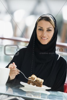 A Middle Eastern woman enjoying a meal in a restaurant