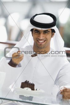 A Middle Eastern man enjoying a meal in a restaurant
