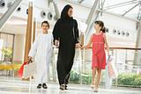 A Middle Eastern woman with two children in a shopping mall