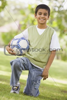 Boy holding football in park