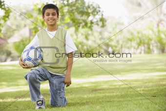 Boy in park holding football