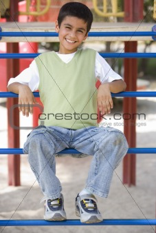 Boy sitting on climbing frame