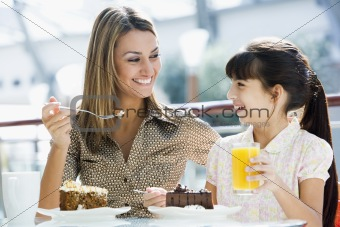 Mother and daughter having cake at cafe