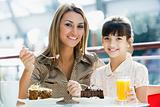 Mother and daughter eating cake in cafe