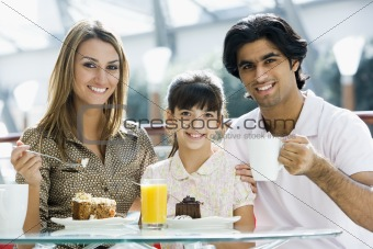 Family eating cake in cafe