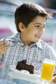 Boy eating chocolate cake in cafe