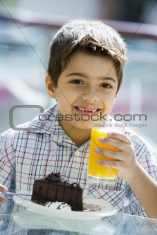 Boy drinking orange juice in cafe