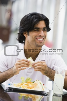 Man eating sandwiches at cafe