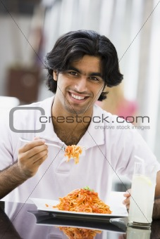 Man eating plate of pasta at cafe