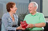 senior couple giving gift