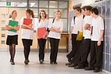 Teenage boys watching girls walk down a school corridor