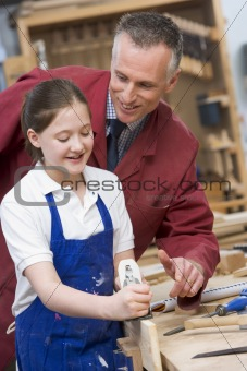 Schoolgirl and teacher in woodwork class