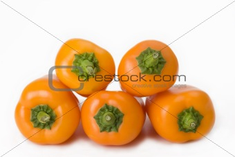 five orange bell peppers on white background