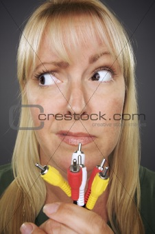 Confused Woman Holding Electronic Cables