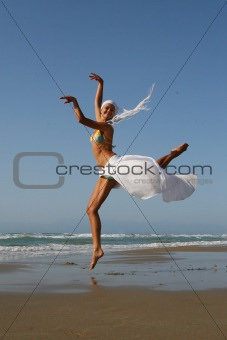 Beautiful young woman jumping on a beach in Greece