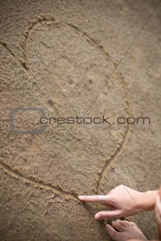 a womans hand drawing a heart on the beach to show the love