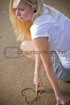blond woman drawing a heart on the beach to show the love