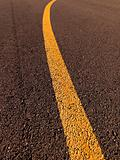 Yellow traffic line on asphalt.