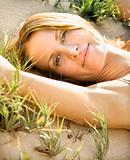 Woman relaxing on sand.