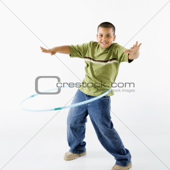 Boy using hula hoop.