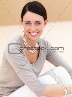Happy young woman sitting on floor