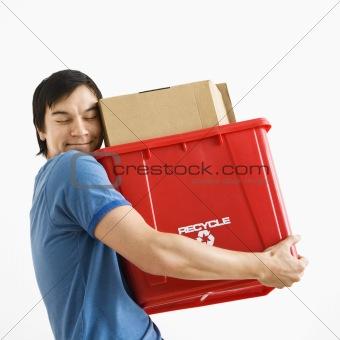 Man hugging recycling bin.
